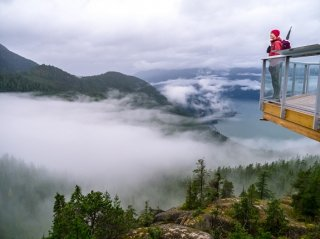 A hiker in a red coat and purple toque standing on the viewing platform near the top of the Sea to Sky Gondola with misty clouds and forest below.