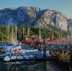 a wooden dock with purple railings and colourful sailboats drifting into the Squamish harbour,  aided by the Stawamus Chief looming when you look at the history.