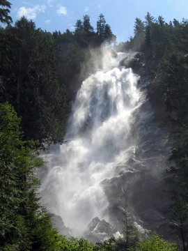 Shannon Falls cascading down with rich green woods surrounding the falls and blue heavens above.